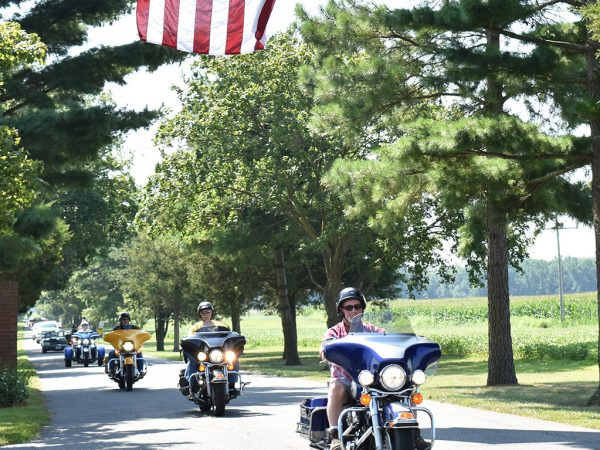 Line of motorcyclists riding under American flag on tree-lined street.