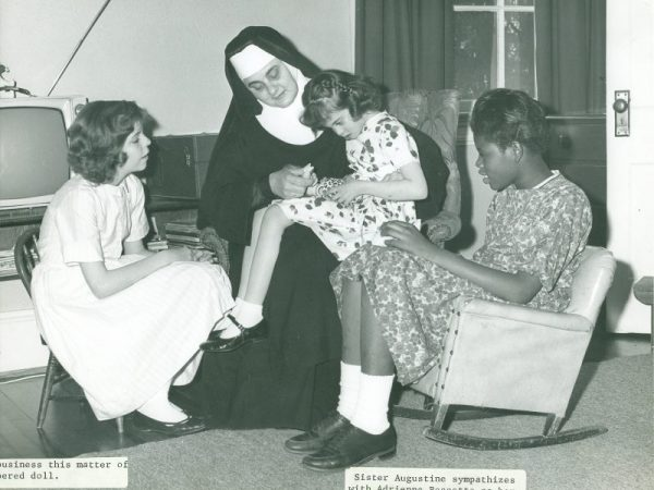 Sister Augustine Kern sitting with three young girls.
